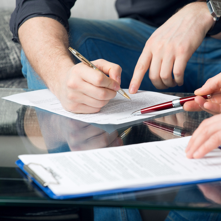 Man signing a legal document on a glass table with a another person pointing a pen on where to sign